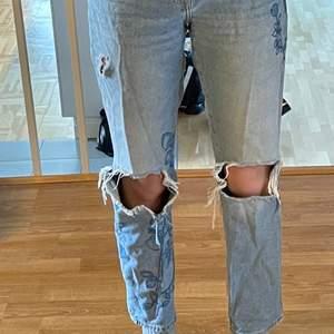 Väldigt snygga ljusblåa högmidjade jeans i mycket bra skick med stora hål på knäna, plus ett litet hål längre upp på benet och ett hål i högra backfickan. Jeansen har jättefina blåa broderade blom- och växt detaljer på båda benen :) Köpta på H&M och är storlek 36 men skulle säga att de passar mycket bra på 38:or också eftersom de är ganska stora i midjan🙂 Kontakta för fler bilder, frågor eller vid intresse!😊 Frakt tillkommer!!