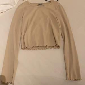 En superfin beige tröja som har ett håll i ryggen