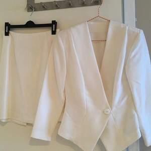 Vit skräddarsydd dräkt i thaisiden (struktur i tyget) storlek 36. Jacka+kort kjol, använd endast en gång, 400kr.