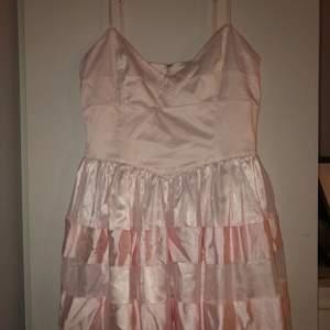 En Rosa korklänning med volang. Aldrig använd i storlek 36. Köpt på Ginatricot.