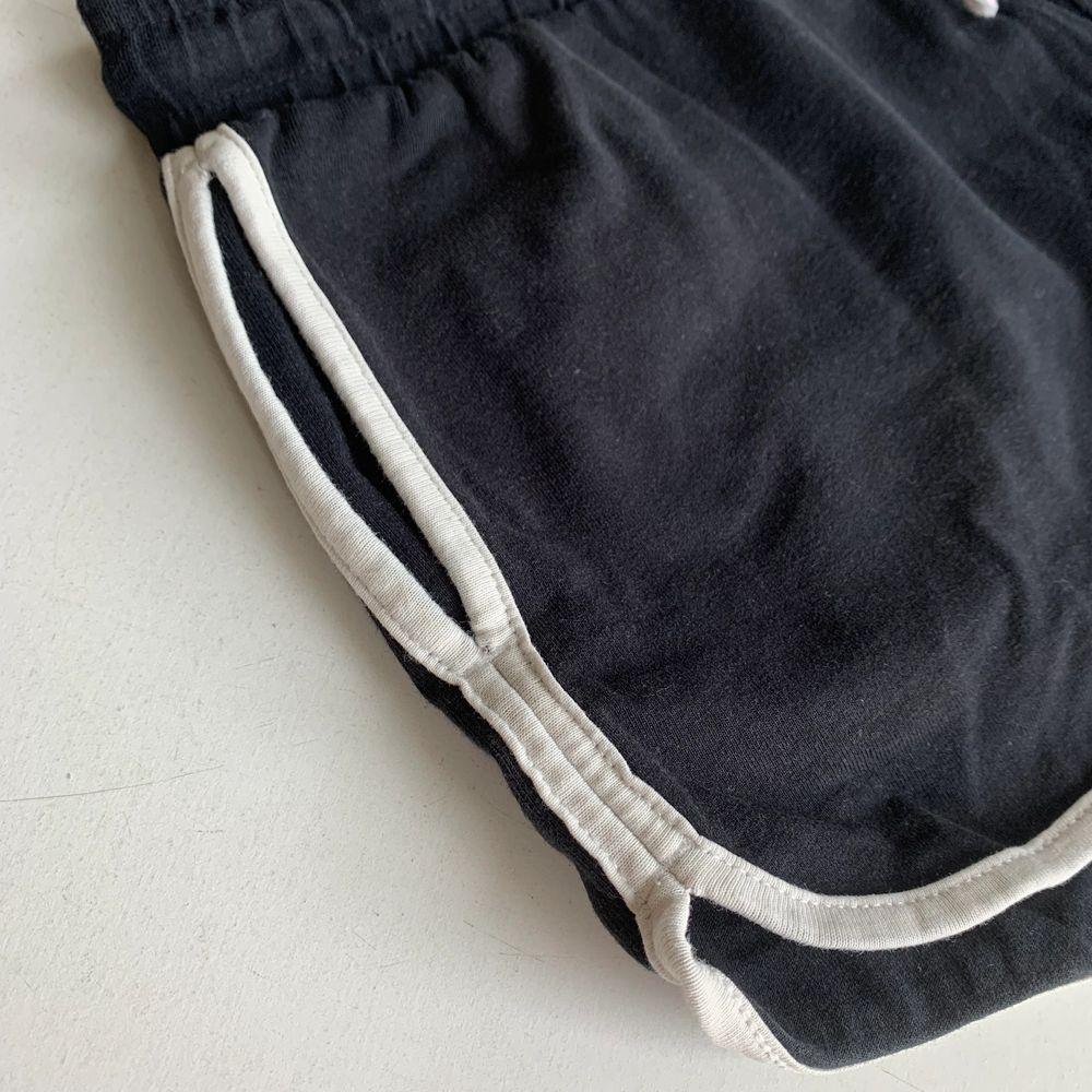 Svarta shorts med vit kant. Vita och guldiga snören i midjan och fickor på sidorna. Stl 146/152 från Lindex. Fint skick och skönt material. Byxorna kostar 20 kr, frakt ingår ej. Swipe för fler bilder.. Shorts.