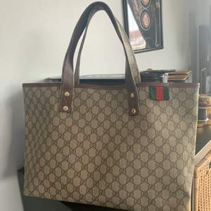100% authentic Gucci Beige/Ebony GG Coated Canvas Signature Web Loop Tote Gucci.   Material: Coated canvas  Hardware: Pale gold  Origin: Italy  Measurements: 17