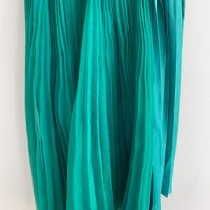 Grön långkjol  Kjolen har flera lager med två olika tyg.  Den har en slits i mitten på sidan  Köparen står för frakten, kan mötas upp i Stockholm city