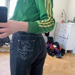 Svart/gråa jeans med silvriga sömmar på ena bakfickan.