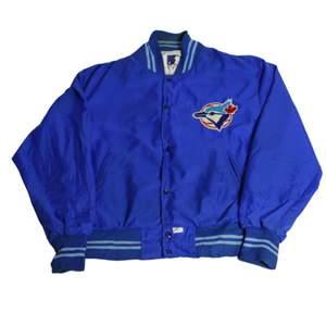 En starkt blå baseballjacka som kommer från usa:s stora baseballliga MLB och ett av deras lag. Är autentisk och väldigt svår att få tag på. Gjord med materialet nylon vilket är perfekt för höst. Thriftad i USA men är i väldigt gott skick.