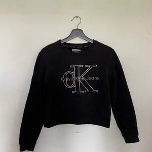 En tjocktröja från Calvin Klein Jeans. Är i bra skick. Är i färgen svart med silvrigt tryck. Storlek XS. Frakt priserna varierar beroende på vart du bor och hur stort paketet är!