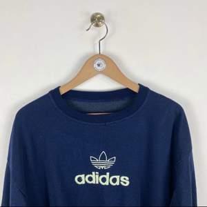 En mörkblå adidas sweatshirt från en vintage sida i England. Köpte den för 500, (+200 frakt). Den är i storlek L och sitter overzised. Denise inga hål eller större slitningar men den är använd och inte så mjuk i materialet.