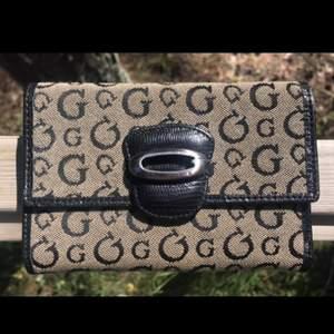 Snygg plånbok från Guess. Endast använd ett fåtal gånger. Så är fortfarande fräsch och fin. Många fack till kort och sedlar och även ett myntfack som inte syns på bild men det finns.
