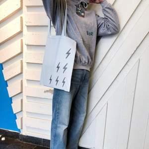 Ljusblå tygväska tillverkad i 100% bomull med ett tryck bestående av 6 blixtrar i en silverfärgad reflex. Centrerat på baksidan är även vår logotyp tryckt i silverfärgad reflex.