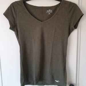 En militärgrön t-shirt från hollister med v-ringad halslinning. I bra skick och skönt material! Storlek XS, passar även S.