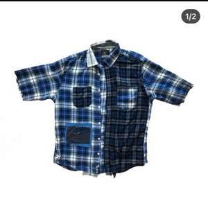 en kortärmad skjorta som är omgjord av material frn andra skjortor och jeans! Plaggets längd är ca 66 cm.