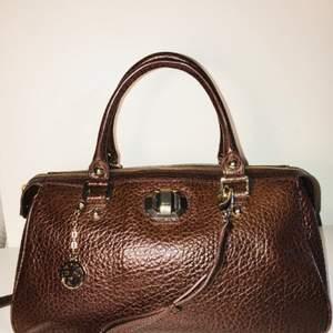 DKNY Väska  Väska i läder från DKNY i mycket fint skick. Inga märken på användning. Knappt använd!  Färg, mörkt Brunt  Material: Läder  Mått: Höjd: 22cm           Längd: 39cm           Bredd: 19cm