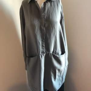 Grå skjortklänning från Wera instorlek 40. Passar 36-40. Siden. Det är en liten fettfläck på den som inte får bort. Annars i gott skick.