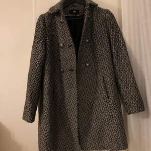 """Gullig """"manschett-kappa"""" i vit/svart mönster. Försiktigt använd. Krage, fickor, innertyg. Väldigt lyxig känsla!"""