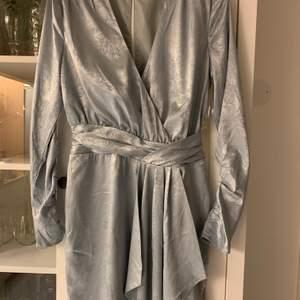 Snygg klänning i silkes/satinliknande material med dovt mönster. Aldrig använd i nyskick. Köpare står för frakt om upphämtning ej är ett alternativ.