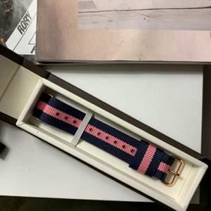 Klassiskt äkta Daniel Wellington klockband i rosa och marinblå. Perfekt skick! Ingår låda (men ingen klocka!).