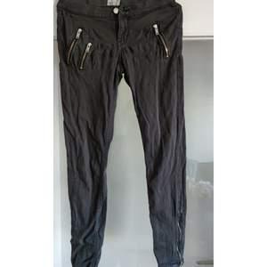 Grå väl använda men fortfarande fina jeans från Gina Tricot i storlek 38 ,  guldiga dragkedjedetaljer och låg midja.