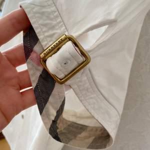 Äkta Burberry skjorta passar storlek S/M. Vit med gulddetaljer och de klassiska Burberry rutorna på insidan av ärmarna. Mycket fint skick! En klassisk och tidslös skjorta som passar till allt! Perfekt basplagg i garderoben. FRAKT INGÅR.