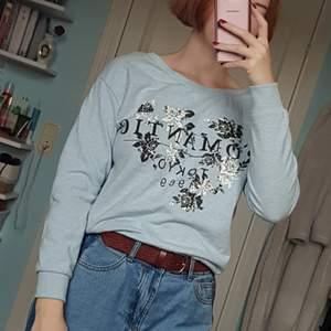 Ljusblå sweatshirt med stort tryck på framsidan