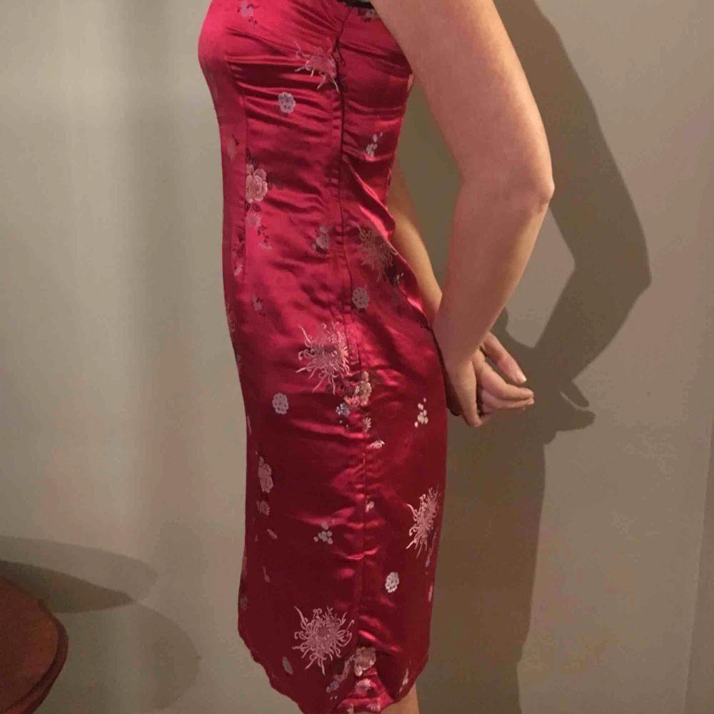 Rosaröd klänning med blommönster i kinesisk stil med fina detaljer och sidenmaterial . Klänningar.