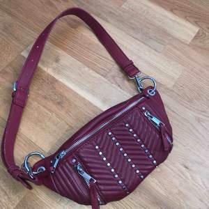 Skitsnygg vinröd magväska/axelremsväska från Zara med silvriga detaljer. Säljes då den tyvärr inte kommer till användning