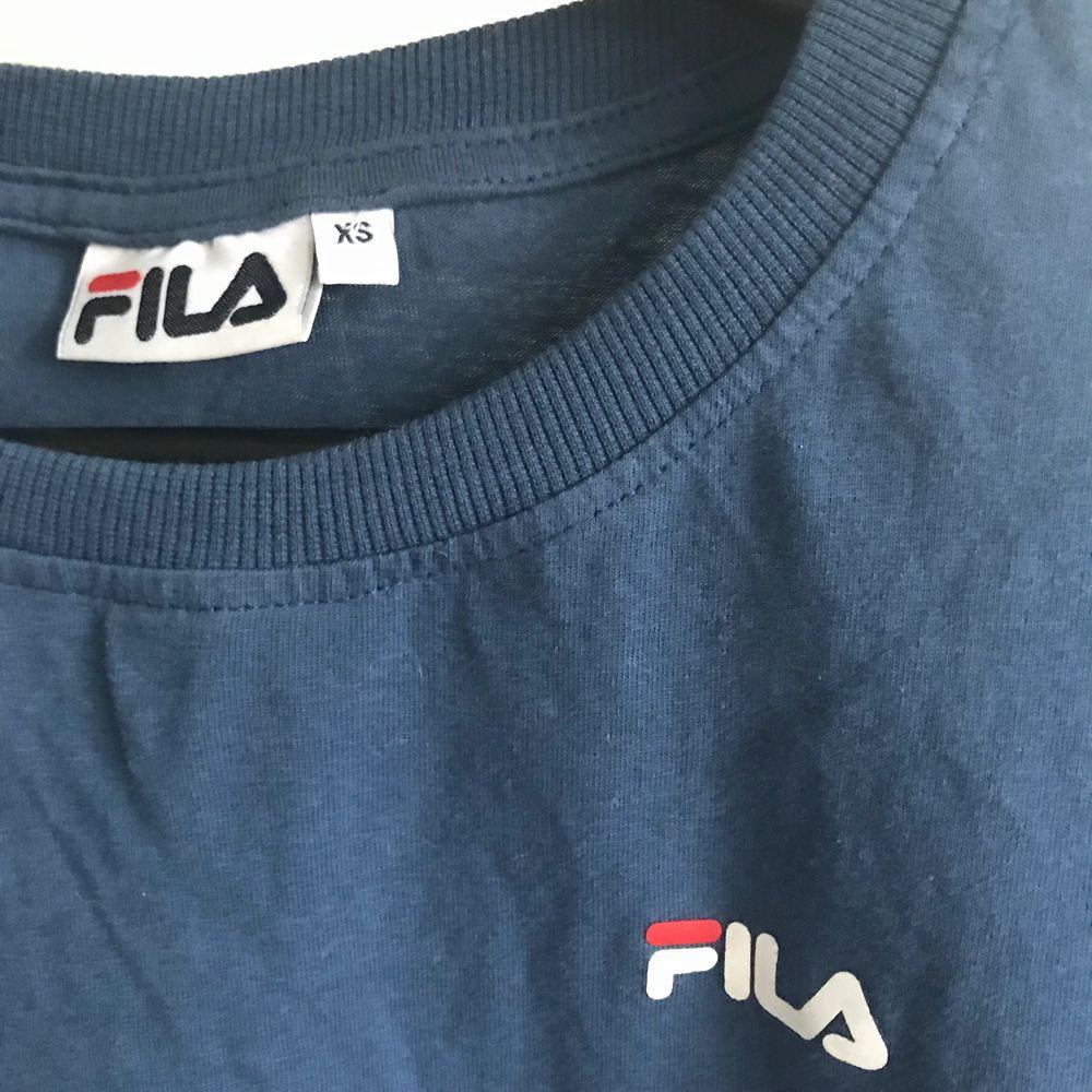 Blå Fila t-shirt som köptes för cirka 300kr säljes nu för 70kr. Fortfarande i bra skick knappt använd. Priset kan diskuteras och köparen står för frakten💕. T-shirts.