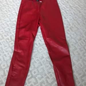 Ett par röda fake skinbyxor som är gjord av ett tjockare material och som passa bättre med i vintern när det är kallt. Byxorna har dragkedjor på slutet av benen och har ingen knapp upptill utan det är resorband.