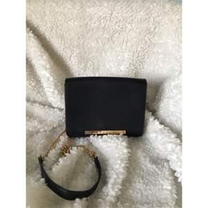 Supersöt svart väska med guldiga detaljer. Vet inte var den är ifrån. Inte jättestor men får plats med ganska mycket i den. Frakt tillkommer.
