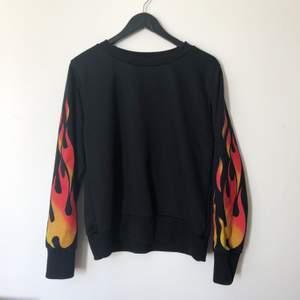 Långärmad tröja med flames på armarna. Några noppror vid muddarna längst ut på armarna, men inget man lägger märke till. Fråga om du undrar något. Frakt tillkommer.