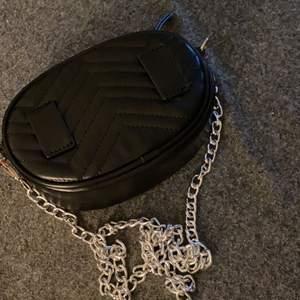 En svart bumbag som man även kan använda som axelväska från Glitter