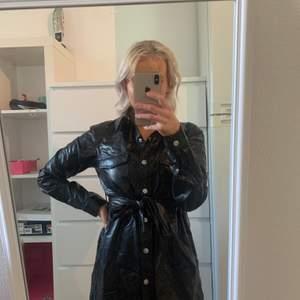 Lång, svart skjorta i ett mjukt och tunt läder-liknande material från NAKD. Kan användas som en klänning på mig som är ca 163. Endast testad, nyskick.