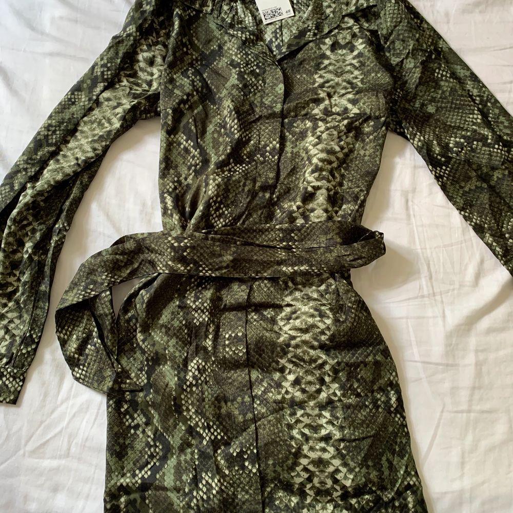 Säljer en oanvänd, grön klänning köpt på h&m! Den är väldigt cool och kan bli nerklädd såväl som uppklädd 🌿 Behösv fler bilder så hör av er! Köparen står för frakten! . Klänningar.