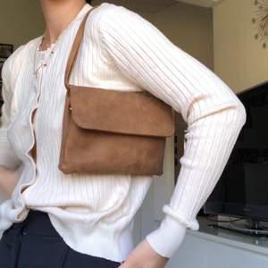 Brun väska som går att ha som axelväska och som crossbody väska! Rymlig med många fack!
