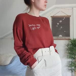 kort och lös tröja i rostrött med texten