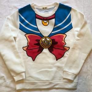 Helt ny oanvänd Sailor Moon tröja. Har lappen kvar. Mjuk och skön, 100% bomull. Säljes pga fel storlek. Är M men sitter mer som S. 150 sek, Frakt ingår!
