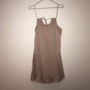 Ljusrosa klänning i sidenliknande material. Jättefin knytning i ryggen, aldrig använd.