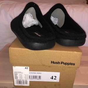 Svarta Hush Puppies tofflor med ovandel och foder i filt.