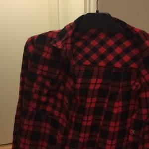Klippt bort lappen men den är mellan S & M Jättefin röd svart rutig skjorta