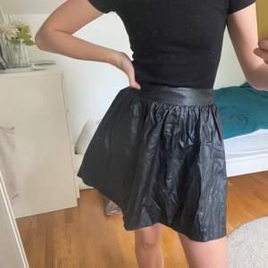 Kjol i skinn/läder-immitation. Från BikBok stl S. Använd fåtal gånger. Frakt ingår. Har resår i midjan på baksidan.