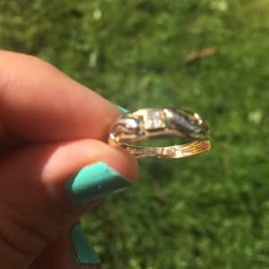 Ring i äkta guld (18k). Ringen är i röttguld (vanlig guldfärg) sedan är delfinerna i vitt-guld. Jag vet tyvärr inte vad det är för sten i mitten.