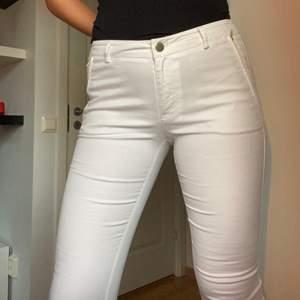 Säljer ett par vita chinos med guld detaljer både vid fickorna och nere vid byxbenet. Byxorna är köpta från Mq och är i nytt skick! Storlek: 38