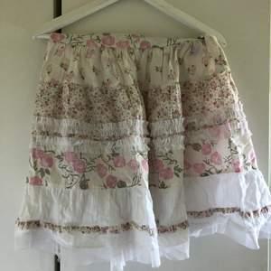 Blommig ljusrosa/vit kjol, passar stl S och M. Mycket fint skick. Skickas mot fraktkostnad 44 kr.
