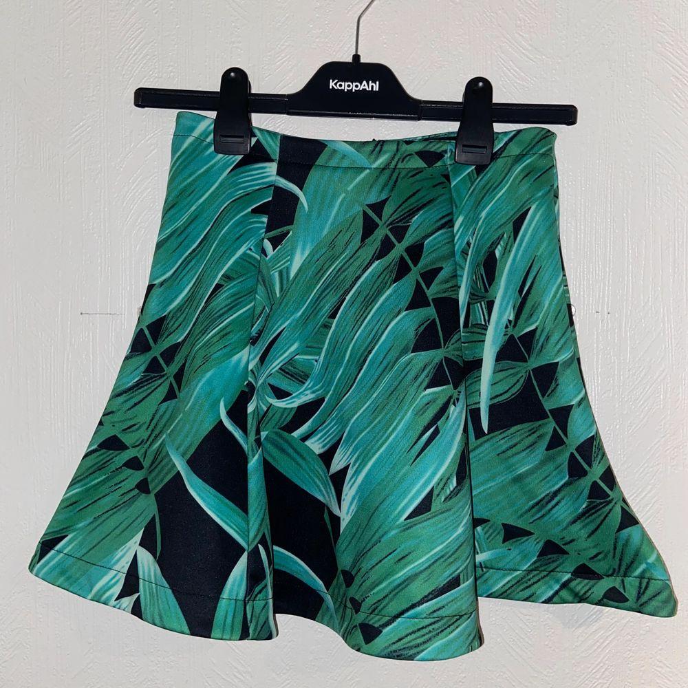 Unik kjol med någon typ av växt/blad på sig. Från bikbok med storlek XS. Väldigt strechig och bra skick då den ej användts.. Kjolar.