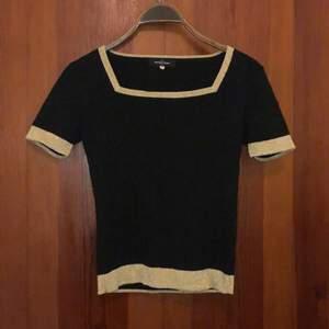 Något croppad t-shirt/tröja i tjockare tyg med guldiga detaljer. Fin kvalité
