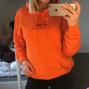 "Trendig orange hoodie med texten ""NO GODS NO MASTERS"" på bröstet. Herrmodell men passar lika bra oavsett kön!"