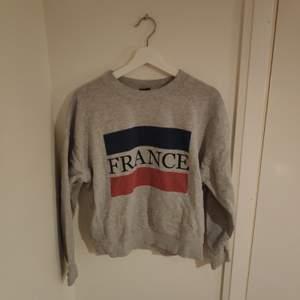 Grå sweatshirt med Frankrikes flagga.