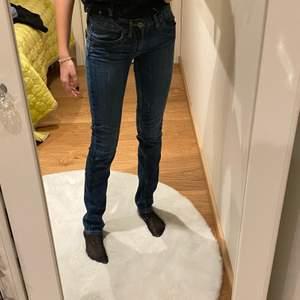 Ganska tight mörk blå jeans. Lösare där nere på benen.