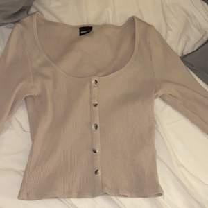 Beige tröja med knappar från Gina Tricot i storlek S. Den är i mycket bra skick. Skön och sitter snyggt.