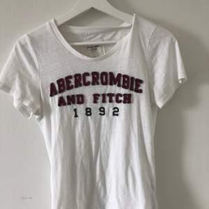Vit T-shirt från Abercrombie med Tryck. Använd ett fåtal gånger, i fint skick✨ 70 kr + frakt