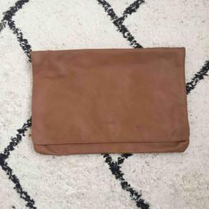 Väska från Monki i fuskläder. Enkel kuvertväska som stängs med knapp.
